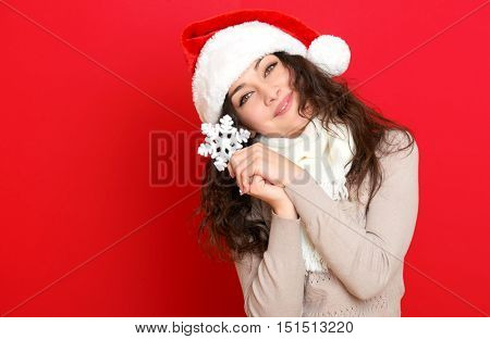 girl in santa hat portrait with big snowflake toy posing on red color background, christmas holiday concept, happy and emotions