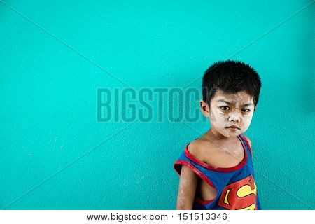 PHANG NGA THAILAND - APRIL 10: Unidentified young asian boy pose agsinst blue wall on April 10 2016 in Ban Bang Pat Phang Nga bay Thailand. Ban Bang Pat is community of fishery and most people are islamist.