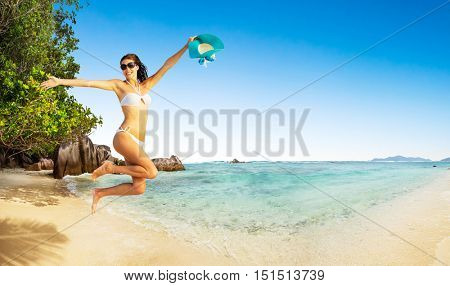 Beautiful young woman jumping in happy mood at tropical beach. Travel and relaxation concept