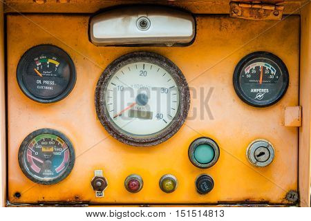 Old yellow rusty machinery/industry control panel. Gauge level and fuel meter. diesel engine.