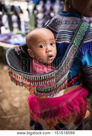 Sapa, Vietnam-September 2016: The innocence of Munk kid in Sapa, Vietnam. Munk mothers usually carry their children on their backs while working.