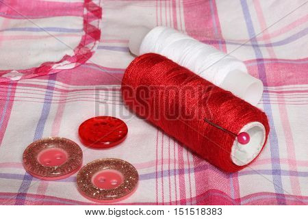 Closeup of red white thread and buttons on a checkered cloth. Sewing accessories.
