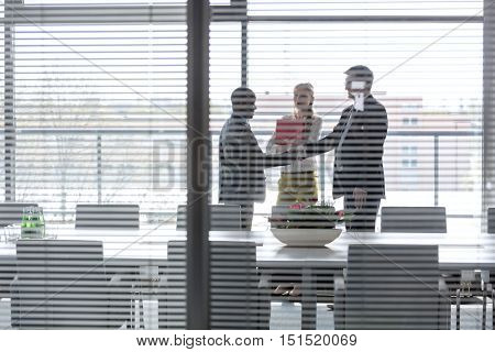 Serious mature businessman talking on mobile phone in office- Corporate Business Portraits of real life business teams