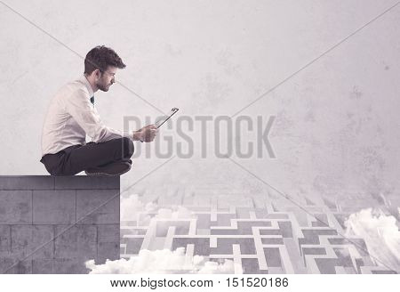 Business worker sitting on concrete building edge, thinking of solving a maze concept with labyrinth and clouds