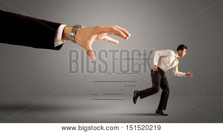 Businessman running away from a huge hand concept on background