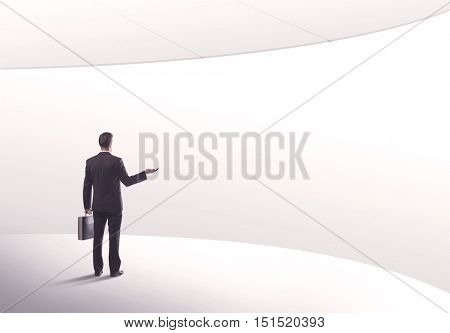 Young sales business person in elegant suit standing with his back in empty white space background with curved lines concept