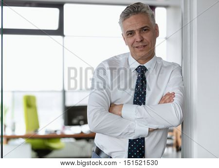 Senior businessman wearing a white shirt in the office looking to the camera with folded arms