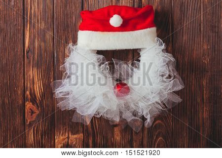Christmas wreath like Santa head from lace and red bauble on the wooden door