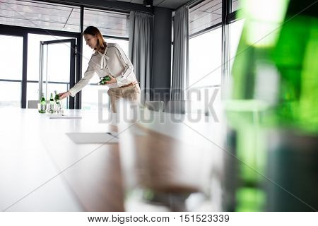 Young businesswoman placing water bottles on conference table in office