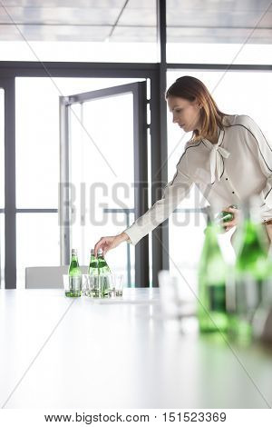 Young businesswoman arranging water bottles on table in board room