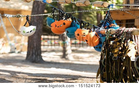 Safety equipment. Special safety helmets hanging upside down on the rope in the adventure park