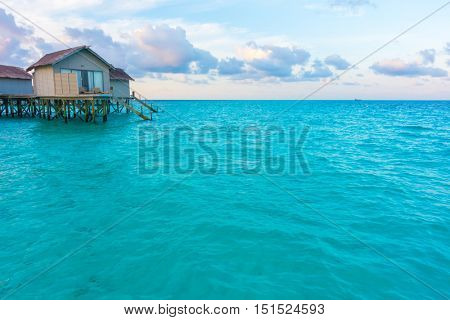 Beautiful sunrise with  water villas  in tropical Maldives island