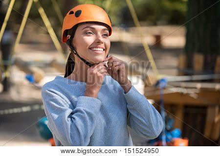 Necessary thing. Beautiful elated young woman smiling and wearing a helmet while getting ready to climb