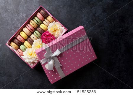 Colorful macaroons and flowers on stone table. Sweet macarons in gift box. Top view with copy space