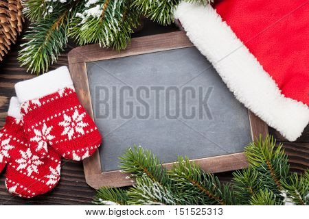Christmas chalkboard, santa hat, mittens and fir tree on wooden table. Top view with copy space for your text