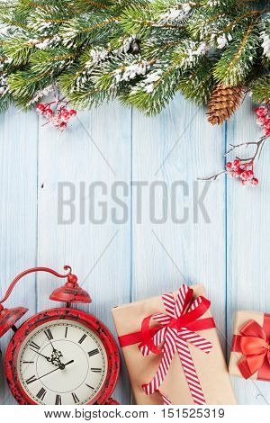 Christmas wooden background with snow fir tree, alarm clock and gift boxes. Top view with copy space