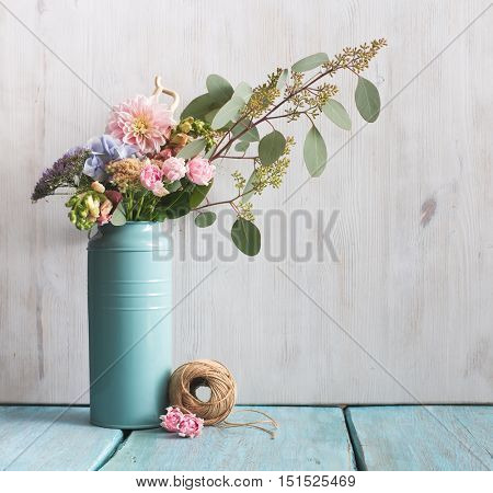 flowers and tree branch in can on blue table, floral composition
