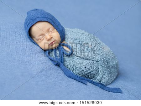 swaddled newborn boy sleeping with blue hood on his head