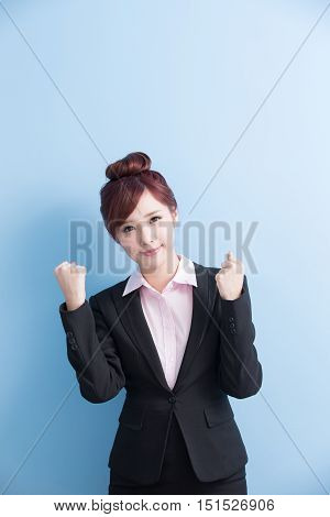 business woman is smile to you and show fist with isolated on blue background asian