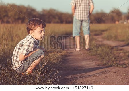 Portrait of sad little boy sitting on the road at the day time.