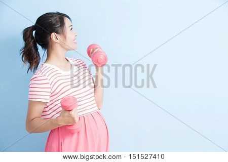 pregnant woman hold dumbell and smile isolated on bluebackground asian