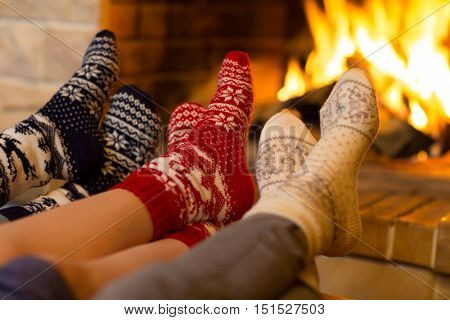 Family in socks near fireplace in winter or christmas time