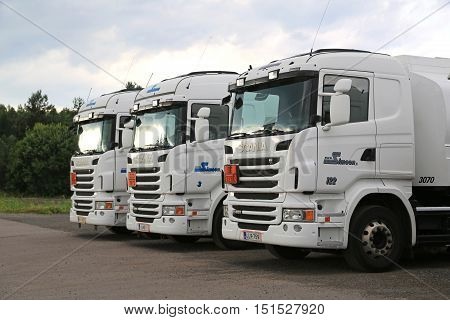 RAJAMAKI, FINLAND - JULY 2, 2016: Fleet of three white Scania R480 trucks with ADR plates parked on a yard in South of Finland.