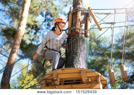 Outdoor games. Cheerful energetic slender woman sitting behind the tree and looking at the rope road while doing adventure climbing