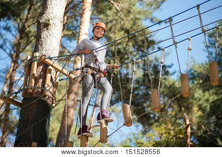 Only forwards. Charming elated well built woman making a step and going forward while holding on the ropes