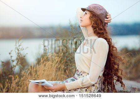 Woman writer concept. Student thinking and looking far afar sitting on ashore on a slope. Joyful happy girl student sitting writing and reading outdoors on the nature.