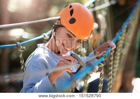 Being cautious. Attractive delighted careful woman holding the mountain carabiner and checking it while thinking about safety