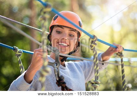 Safety is above everything. Nice positive careful woman holding a mountain carabiner and looking at it while checking the safety equipment