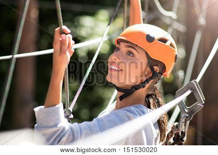 Do not forget about the safety equipment. Pleasant attractive happy woman wearing a special helmet and looking somewhere up while doing climbing activities