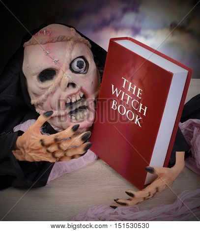 Ghost with scary face has a red witch book in hand.
