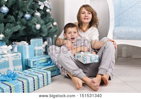 Cheerful Mother And Son In Pajamas Near Christmas Tree With Presents