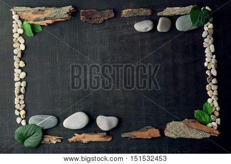 Rectangular frame made of leaves, pebbles and bark on dark background