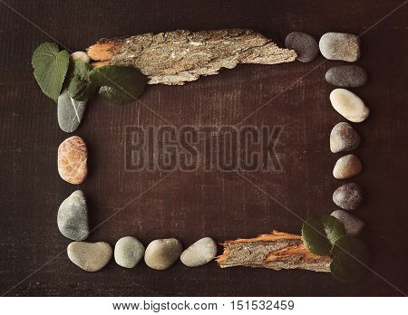 Rectangular frame made of leaves, pebbles and bark on brown background