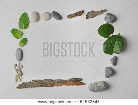 Rectangular frame made of pebbles, leaves and bark isolated on white