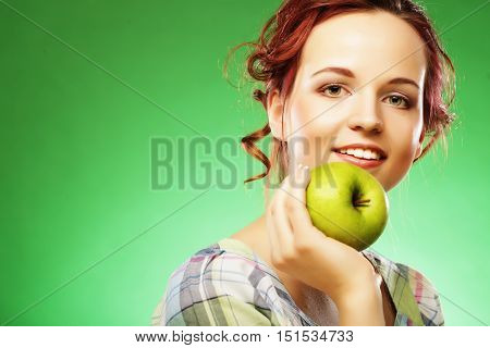 Young happy smiling woman with green apple. Studio shot over green background.