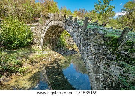 One-arch stone bridge of Captain Arkouda on the river of Xiropotamos. Central Zagori. Epirus Greece