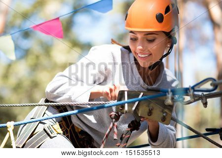 High above the ground. Pretty cheerful young woman holding a mountain carabiner and looking at it while being on the ropeway