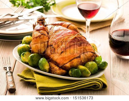 Whole roasted chicken with garlic, potatoes and vegetables in a white ceramic roasting pan food