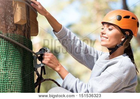 Need to check it. Beautiful cheerful slender woman standing near the tree and looking at her carabiner while checking safety equipment