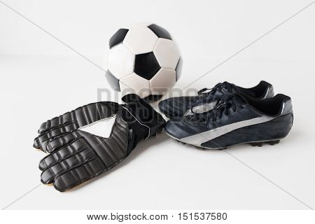 sport, soccer, football and sports equipment concept - close up of ball, boots and goalkeeper gloves over white background