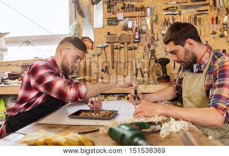 profession, technology and people concept - two workmen with tablet pc computer, dividers or compass and blueprint at workshop