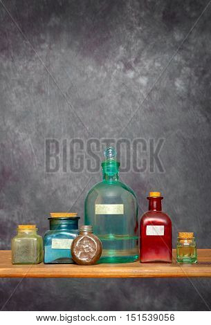 The glass bottles of different form with corks stand on a wooden shelf in a laboratory