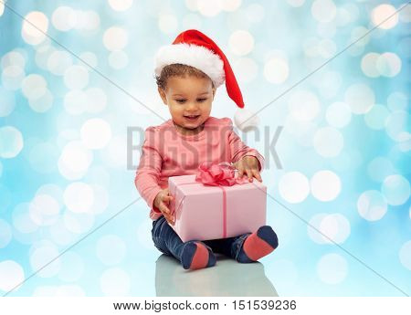 childhood, christmas, holidays and people concept - happy smiling little african american baby girl in santa hat with gift box sitting on floor over blue lights background