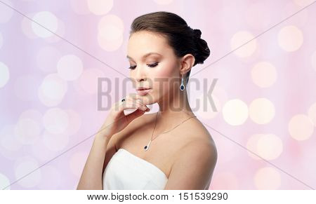 beauty, jewelry, people and luxury concept - beautiful asian woman or bride with earring, finger ring and pendant over rose quartz and serenity lights background