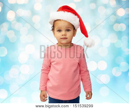childhood, christmas, holidays and people concept - beautiful little african american baby girl in santa hat over blue lights background