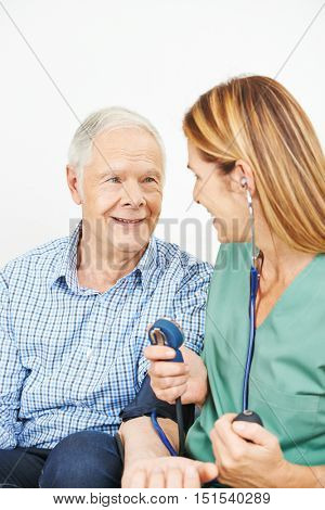 Nurse doing blood pressure monitoring for senior man at home